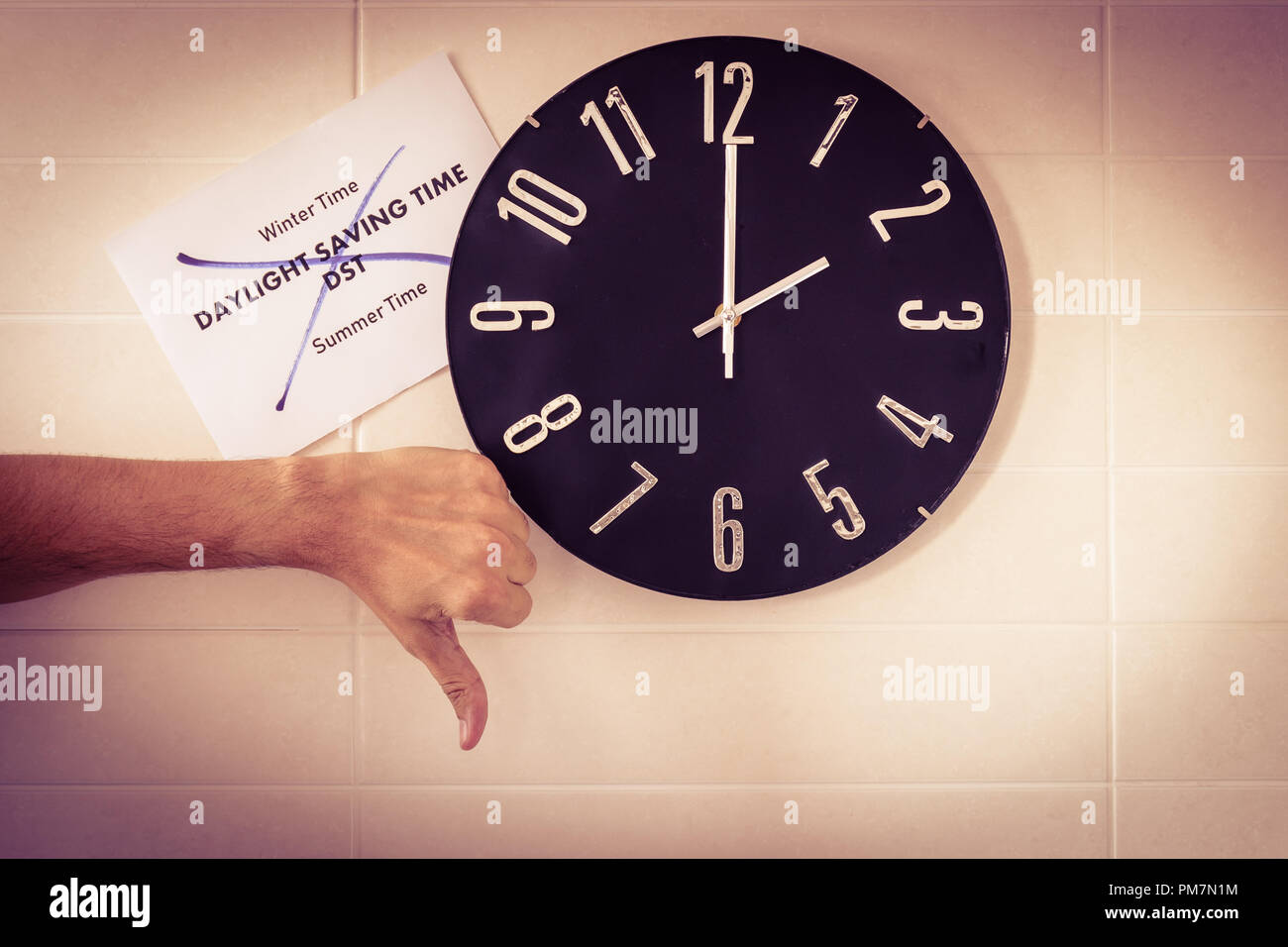 Big black clock on white wall. Time change. DST. Survey of the European Union. Gesture of disagreement . Thumb down of Caucasian man. English banner. - Stock Image