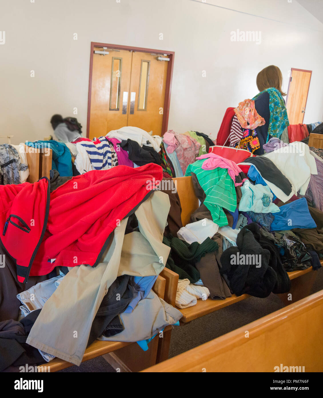 Church group hands out clothing and other items in the chapel of a homeless refuge in North Florida. - Stock Image