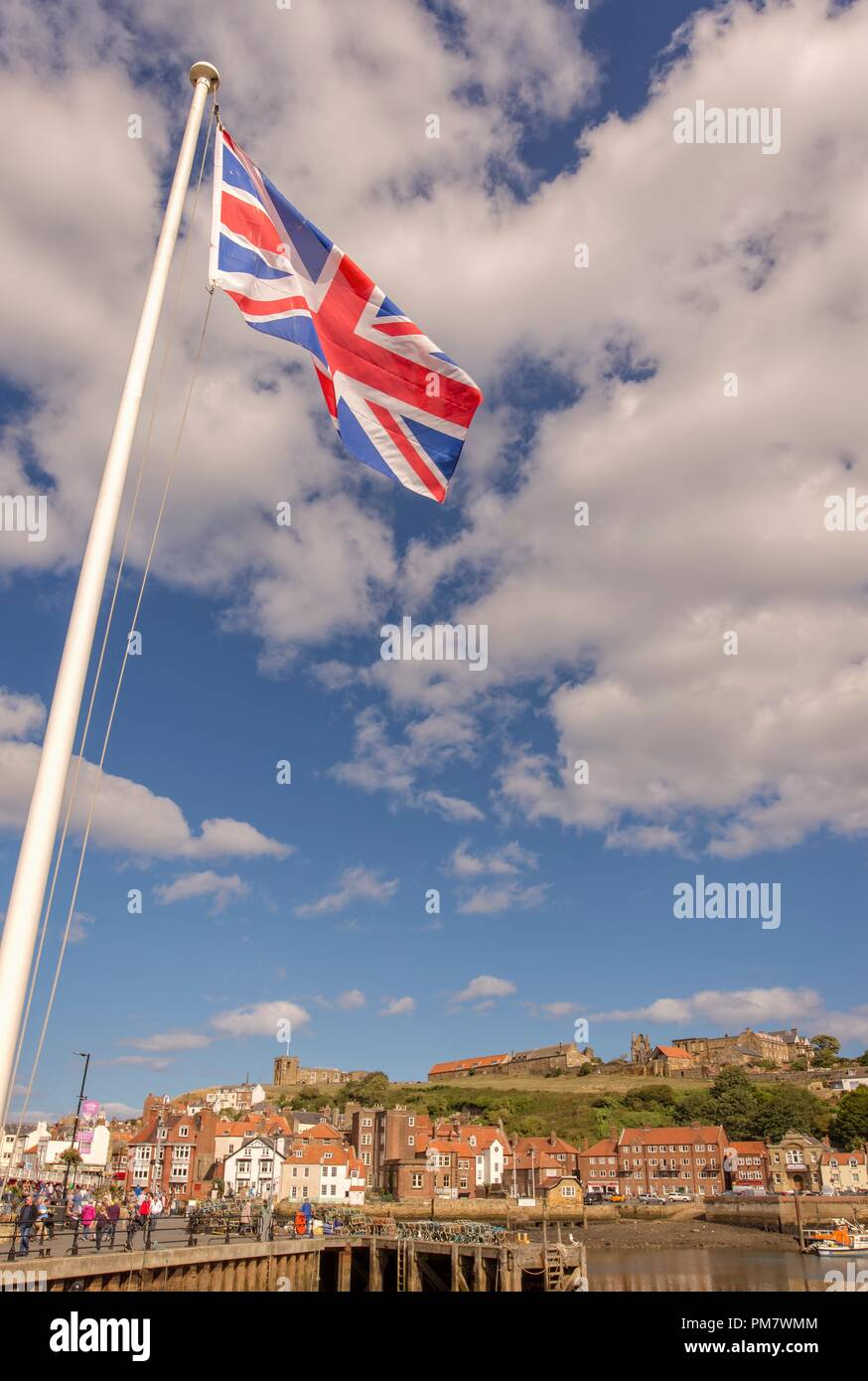 Whitby harbour and town.  The Union flag flies over the scene against a blue sky with dramatic clouds. Stock Photo