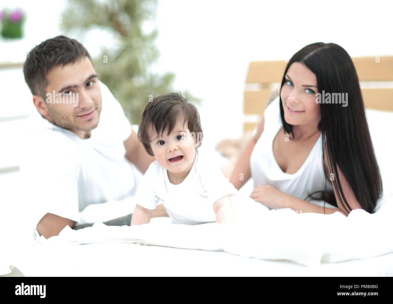 Ð¡harming young family with a toddler lying in bed and smiling - Stock Image