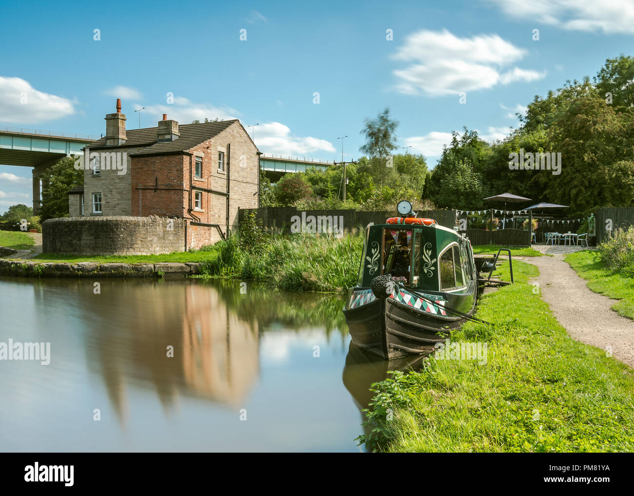 GATHURST, WIGAN, UK AUGUST 31 2018: A photograph documenting a converted canal narrowboat acts as a tearoom with a small outdoor garden seating area o - Stock Image