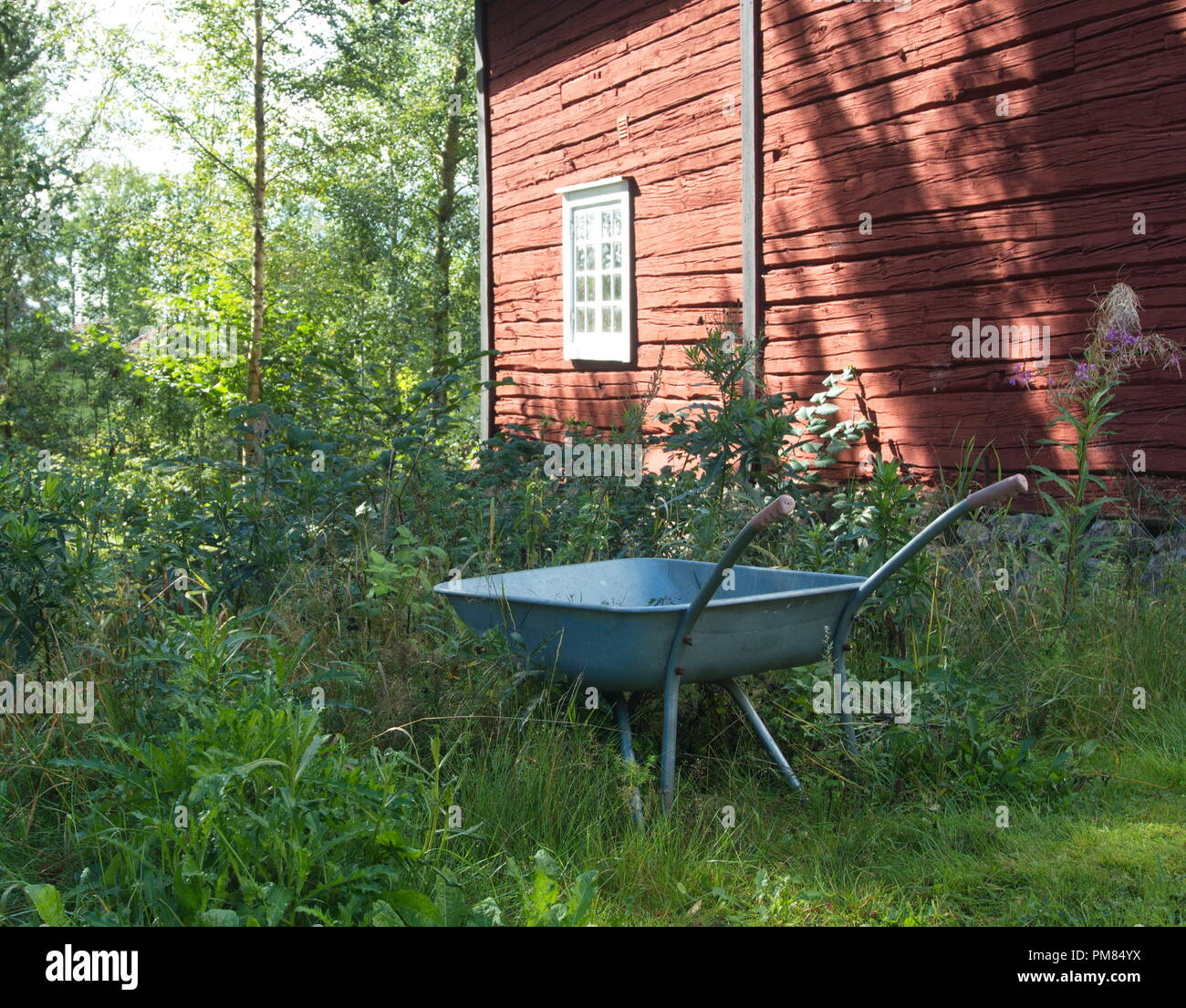 Wheelbarrow with a traditional swedish house in te background. - Stock Image