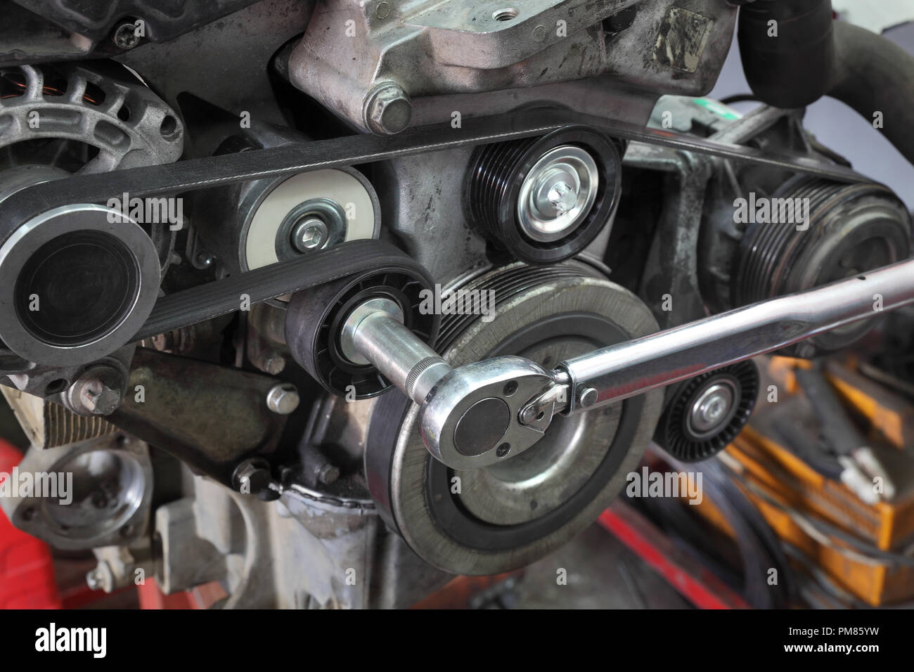 Pk belt, pulleys and alternator at modern car engine after servicing with ratchet tool - Stock Image