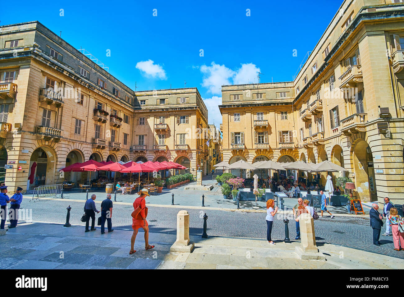 VALLETTA, MALTA - JUNE 17, 2018: The beautiful St John square, located in front of Co-Cathedral, with shady terraces of outdoor restaurants and stone  - Stock Image