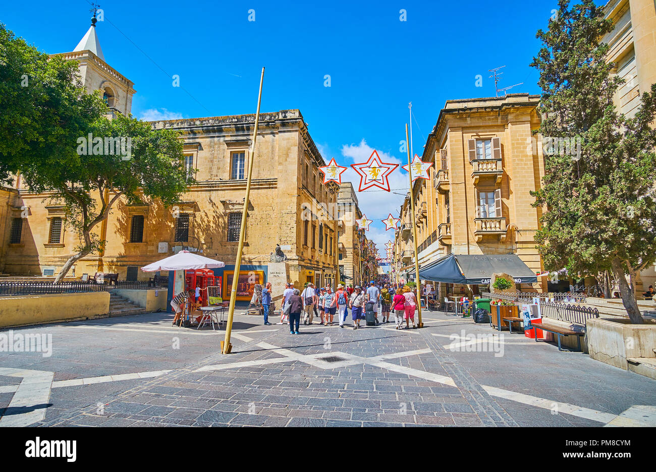 VALLETTA, MALTA - JUNE 17, 2018:  People walk along the medieval mansions and outdoor cafes of Republic street, located in heart of old town, on June  - Stock Image