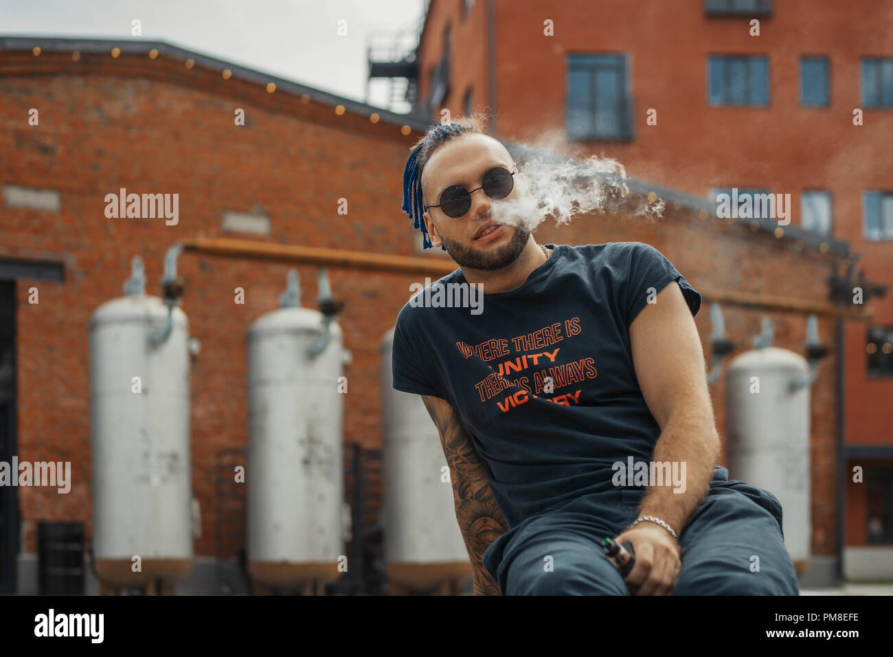 Portrait of young vaping man with dreadlocks. Vapor concept. Vaping e-Cigarette - Stock Image