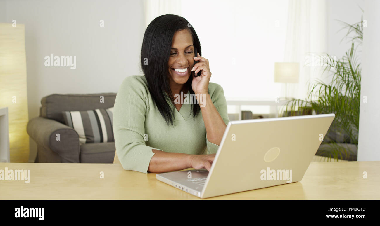 Happy Black woman talking on cell phone while on her laptop