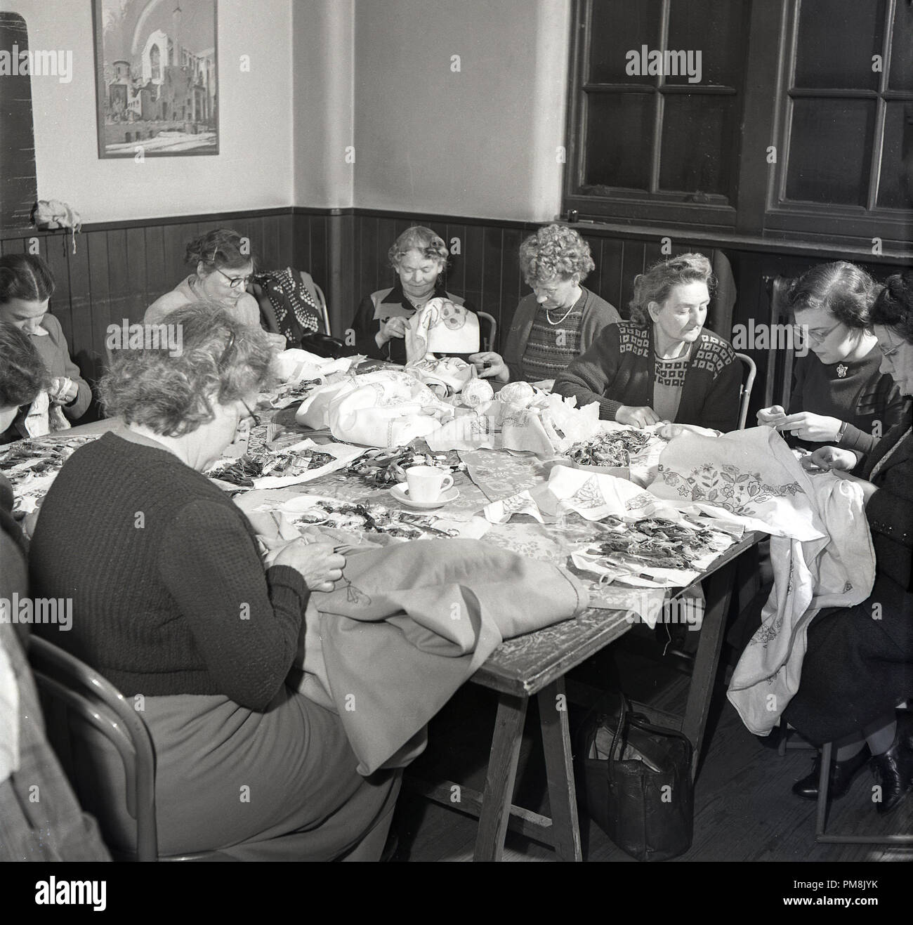 1950s,historical, a group of ladies inside a village hall sitting together around a table doing a decorative sewing or needlework evening class, England, UK. - Stock Image