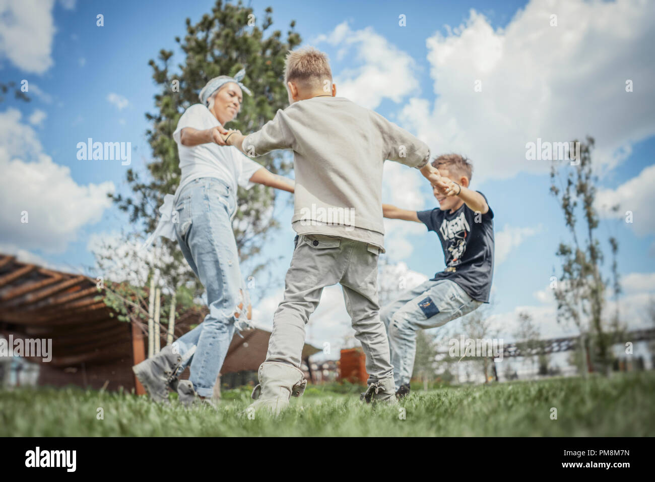 Young blonde mum turning around, whirling with her sons at park. - Stock Image
