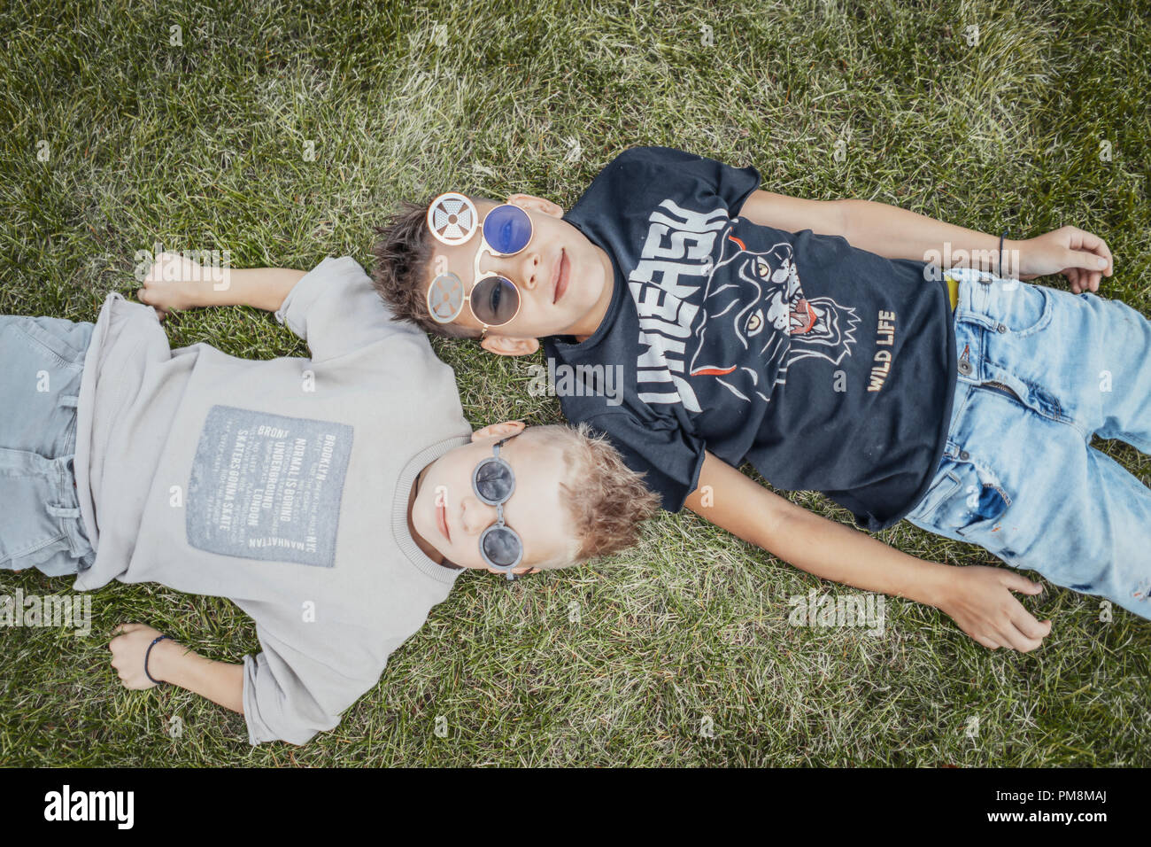Close up of boys, brothers lying in the park on green grass. View from above. - Stock Image