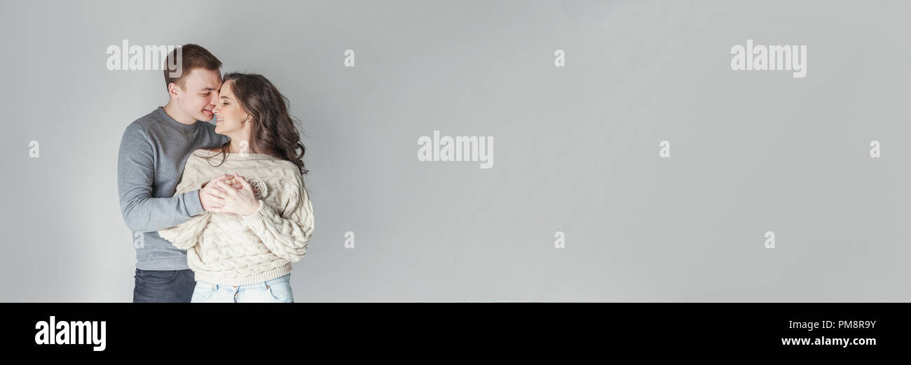 Couple in love having nice time together. Young happy woman hugging boyfriend, white background. Students, bride, groom, engagement, relationship, aspirations, supporting relying concept Banner Stock Photo