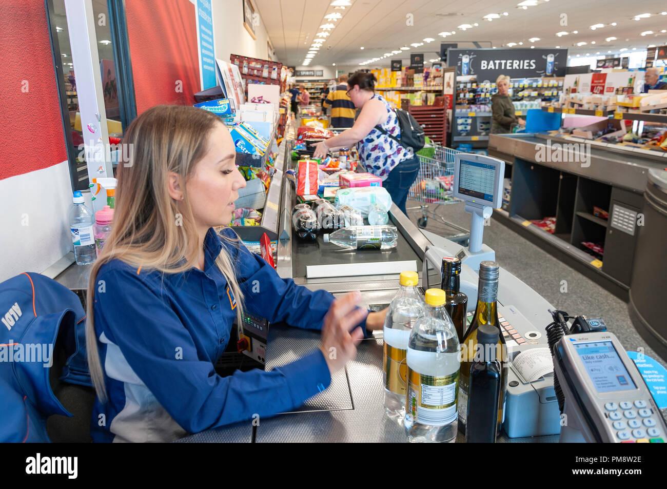 Female check-out counter worker in Aldi Supermarket, Gogmore Lane, Chertsey, Surrey, England, United Kingdom - Stock Image