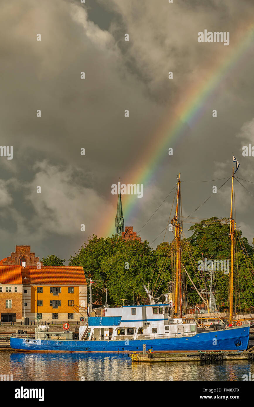 A rainbow rises over a docked ship in Helsingor, Denmark. - Stock Image