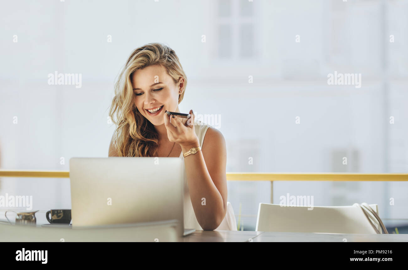 Businesswoman working on laptop computer at a cafe and making phone calls. Blonde female at coffee shop talking on cell phone and working on laptop. - Stock Image