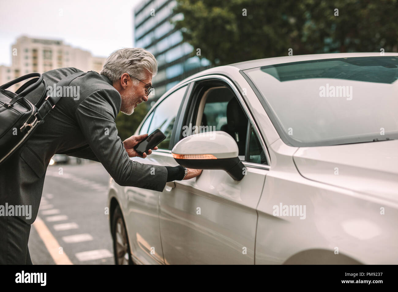 Senior man standing on road and talking to taxi driver through opened car window. Man taking a cab for traveling. - Stock Image