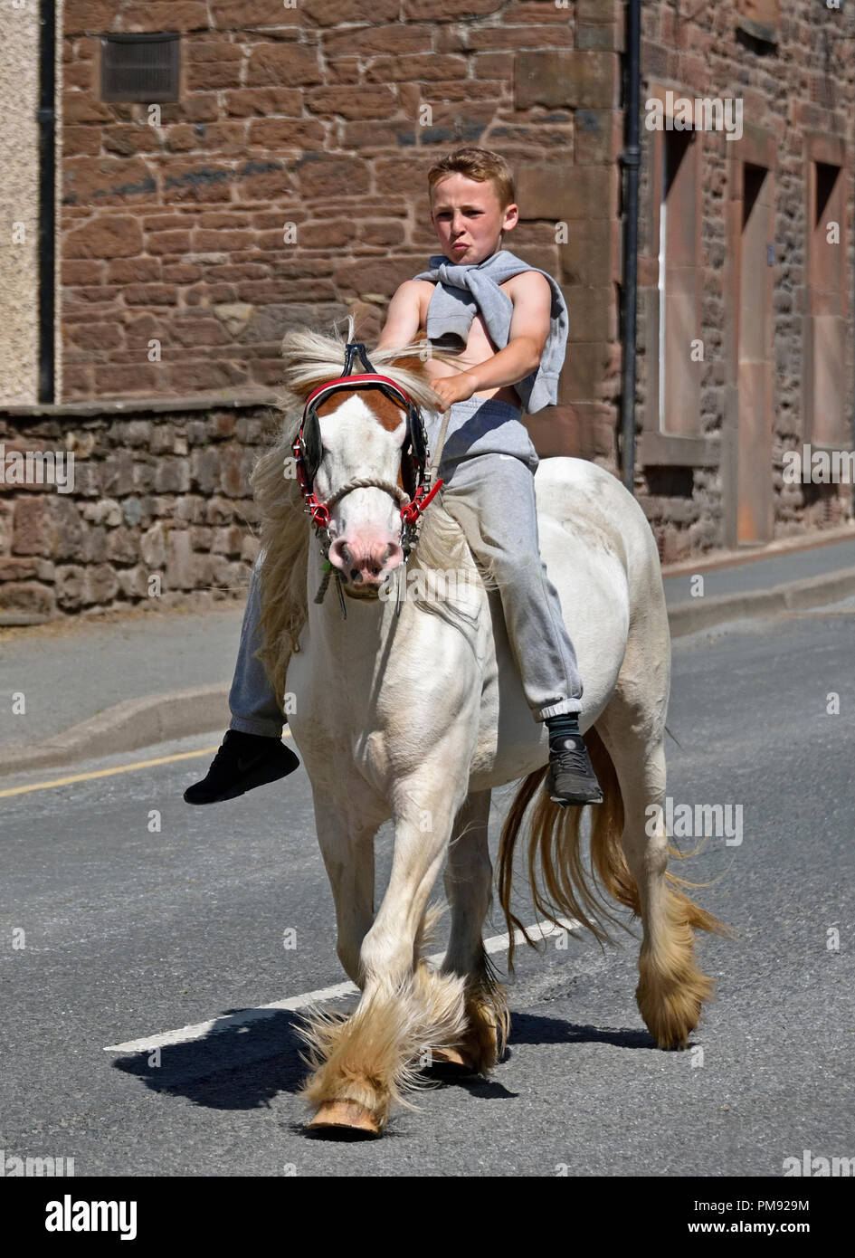 Gypsy Traveller boy riding horse. Appleby Horse Fair 2018. The Sands, Appleby-in-Westmorland, Cumbria, England, United Kingdom, Europe. - Stock Image