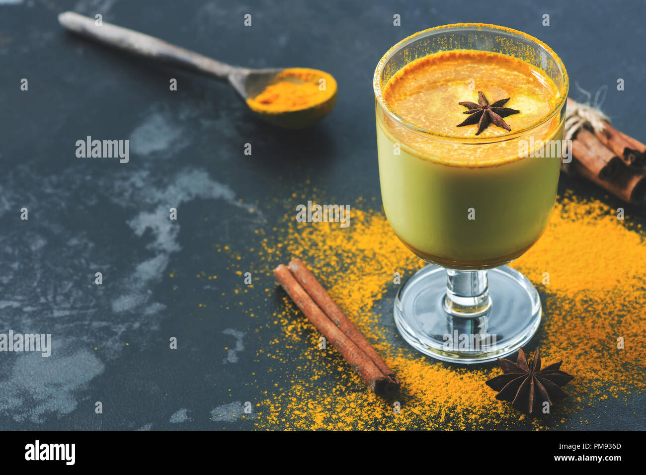 Golden milk, beverage with turmeric and spices in a glass. Drink an antioxidant against the common cold. Copy space, selective focus - Stock Image