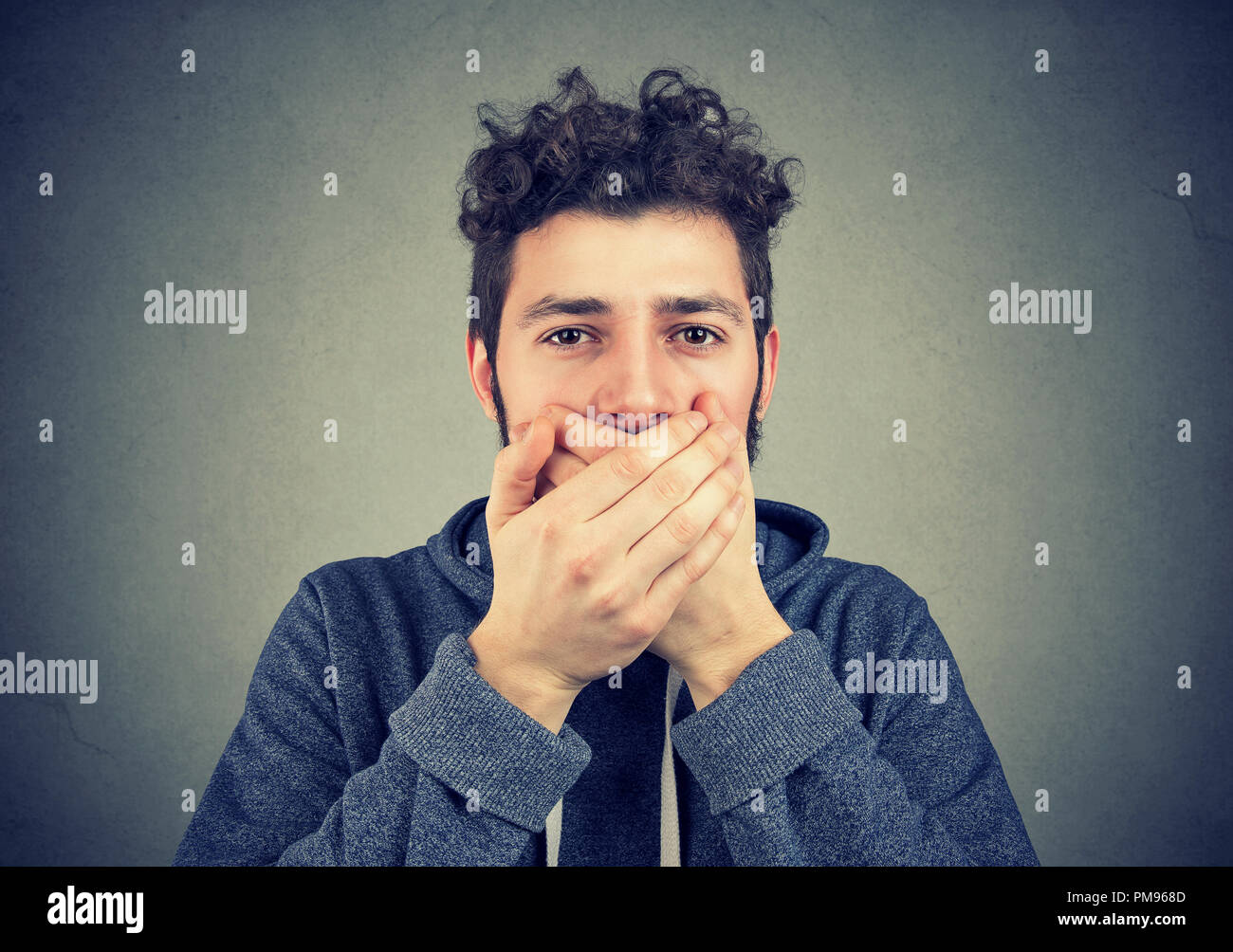Young hipster man covering mouth keeping privacy and speaking no evil - Stock Image