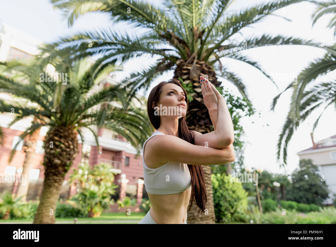 Young woman doing Yoga outdoors in park in white sportswear. Active vacation. - Stock Image