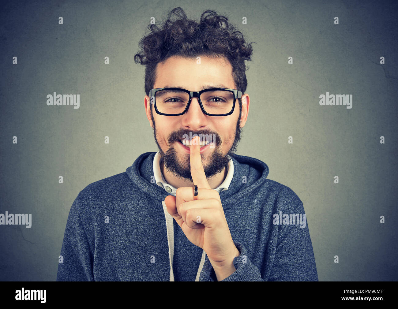 Young hipster man in eyeglasses holding finger on lips asking for silence and smiling at camera on gray background - Stock Image