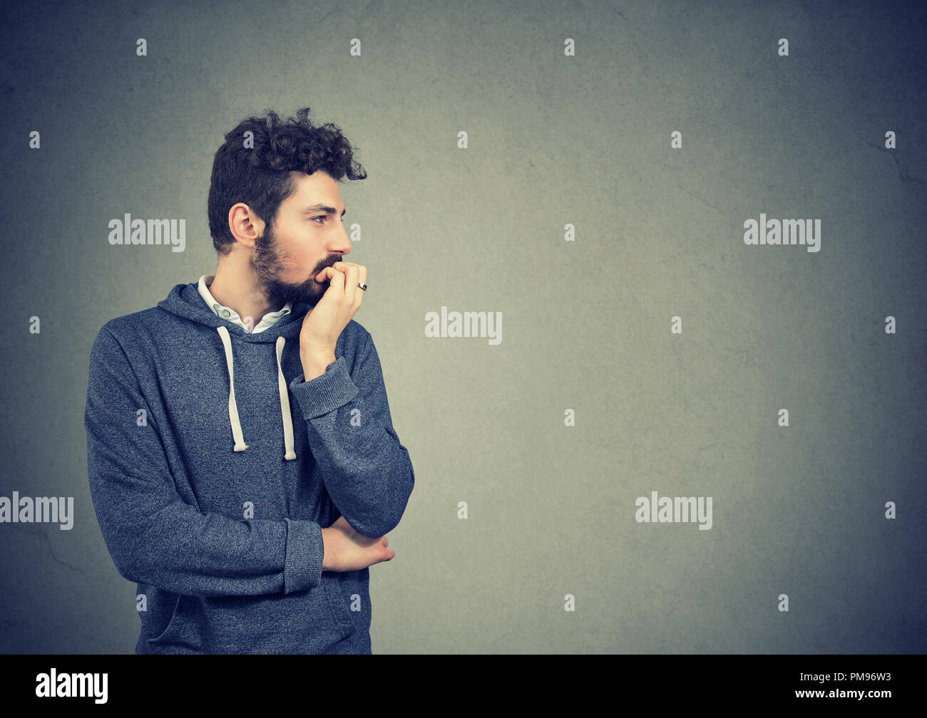 Preoccupied anxious young man biting his fingernails - Stock Image