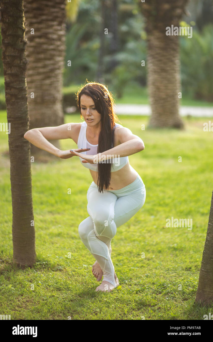 Woman in white sports outfit performing Yoga Eagle pose outdoor, in park meadow. - Stock Image