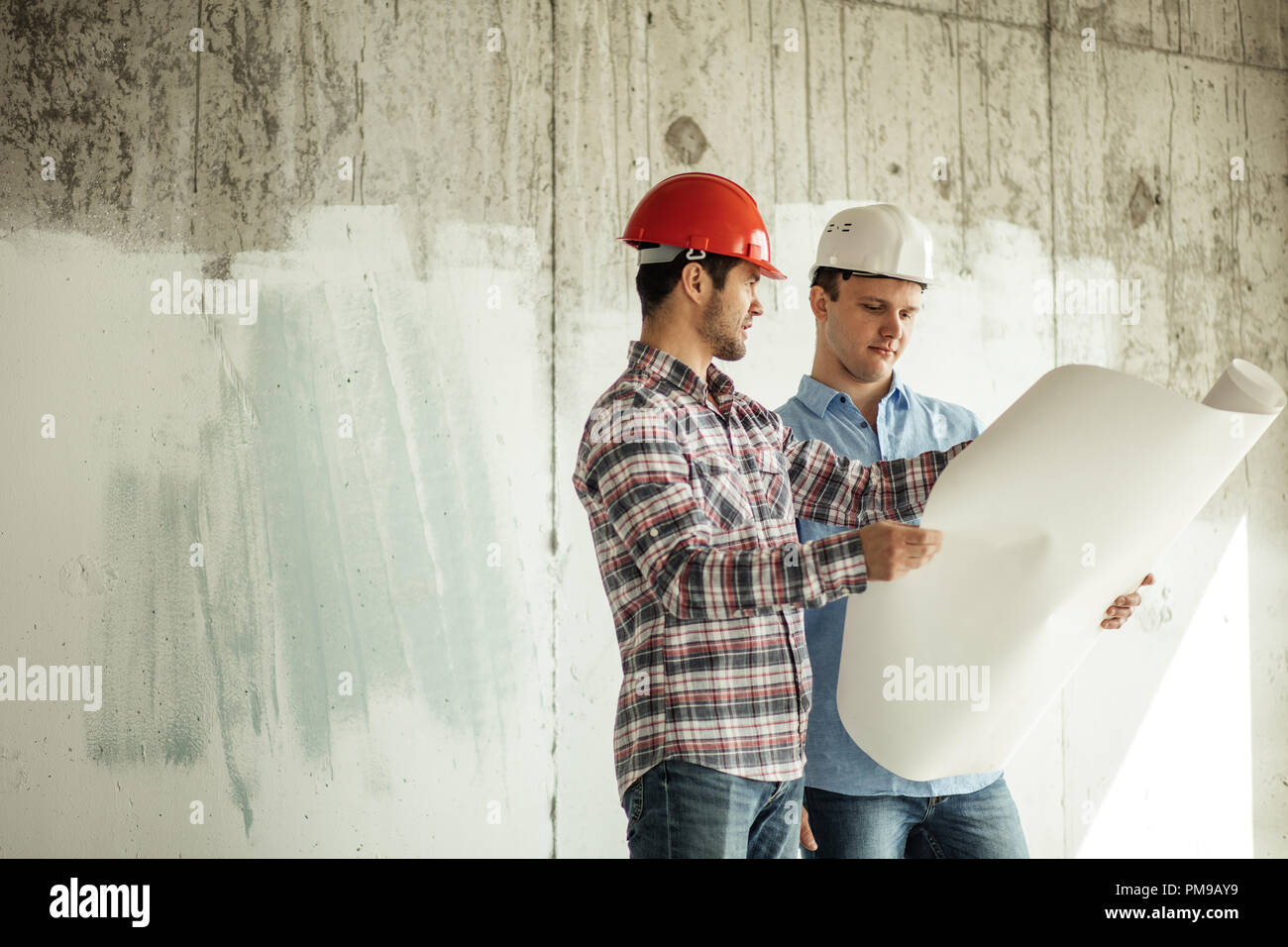 two creative builders are discussing the lotation of a new building. - Stock Image
