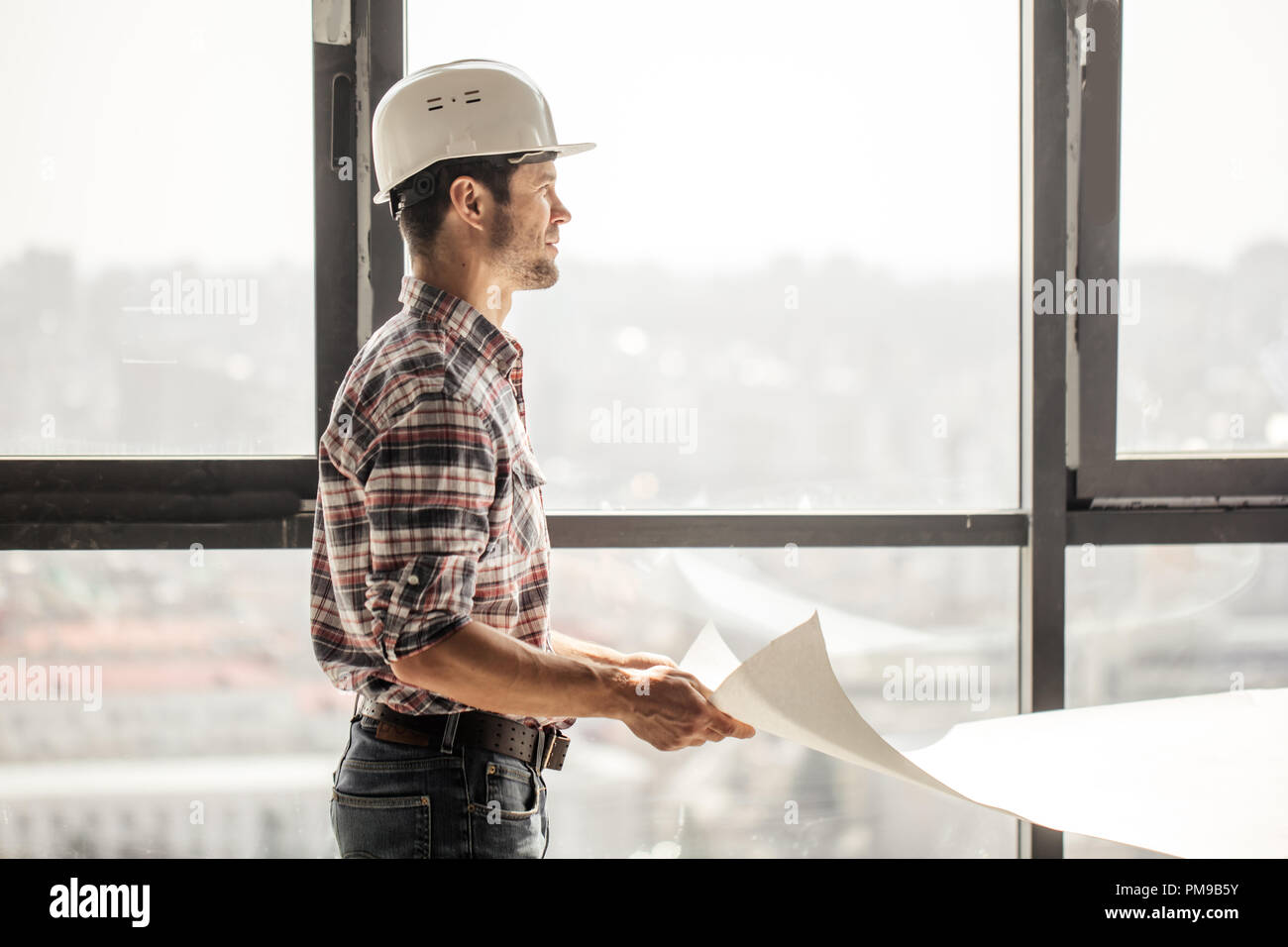 handsome builder is looking away and slitting his eyes - Stock Image