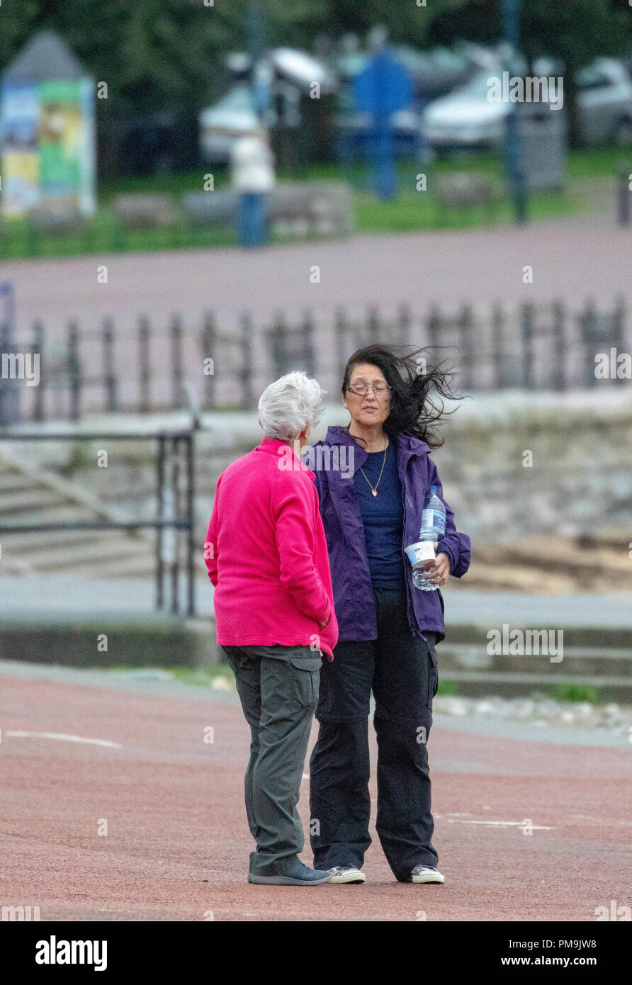North Wales,  September 2018. UK Weather: A Met Office Yellow Warning is in place for windy weather and coastal gales for North Wales as ex-Hurricane Helene makes landfall across the region.  Friends chatting in the windy weather on the coastal promenade of Llandudno, North Wales - Stock Image
