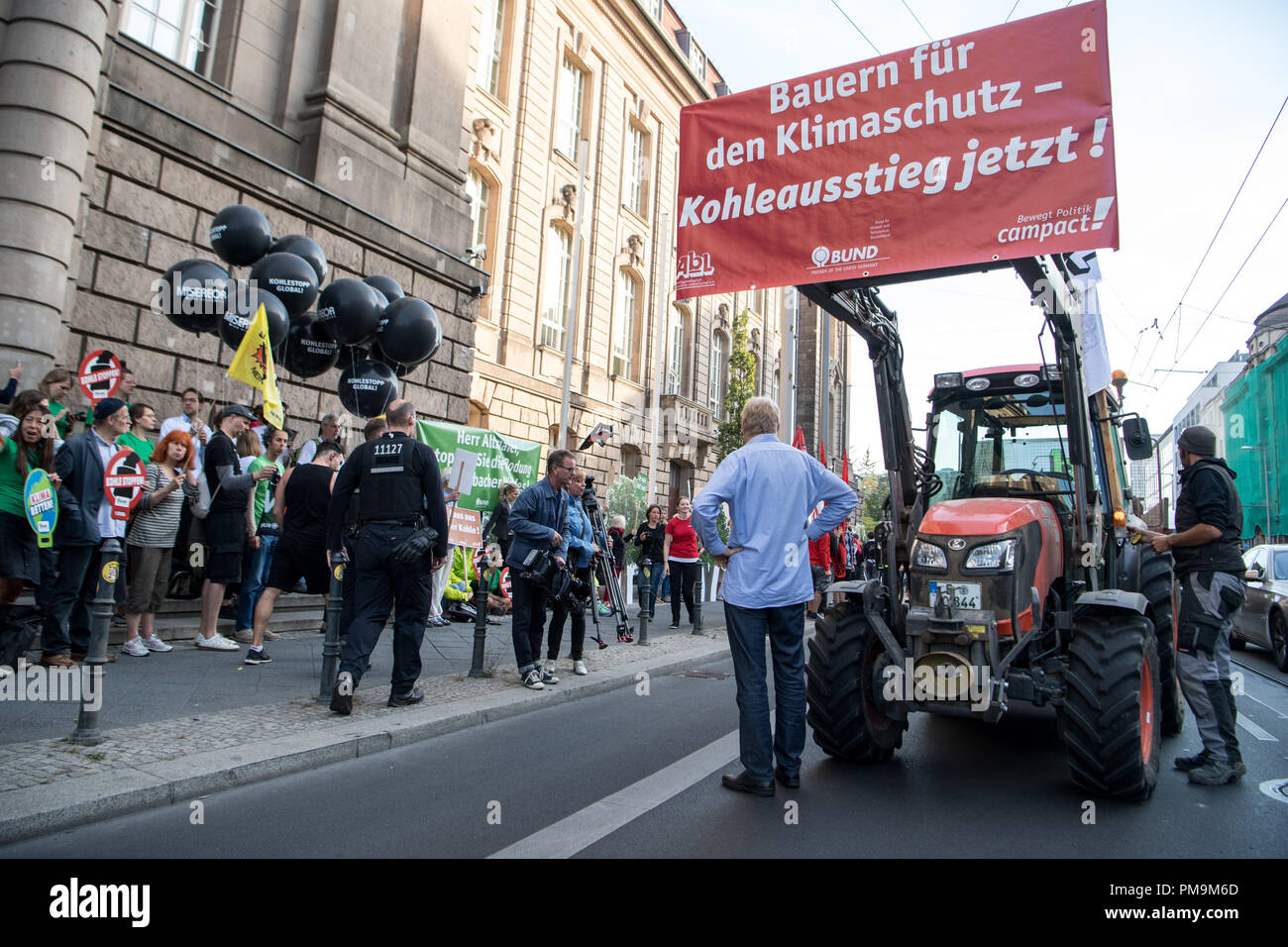 """18 September 2018, Berlin: Several tractors are on the campaign """"tractor against lignite"""" by the organisation """"Campact"""" in front of the Federal Ministry of Economics. Before today's meeting of the Coal Commission, the activists protest against the deforestation by RWE in the Hambach forest and call for the immediate phasing out of coal. Photo: Fabian Sommer/dpa Stock Photo"""