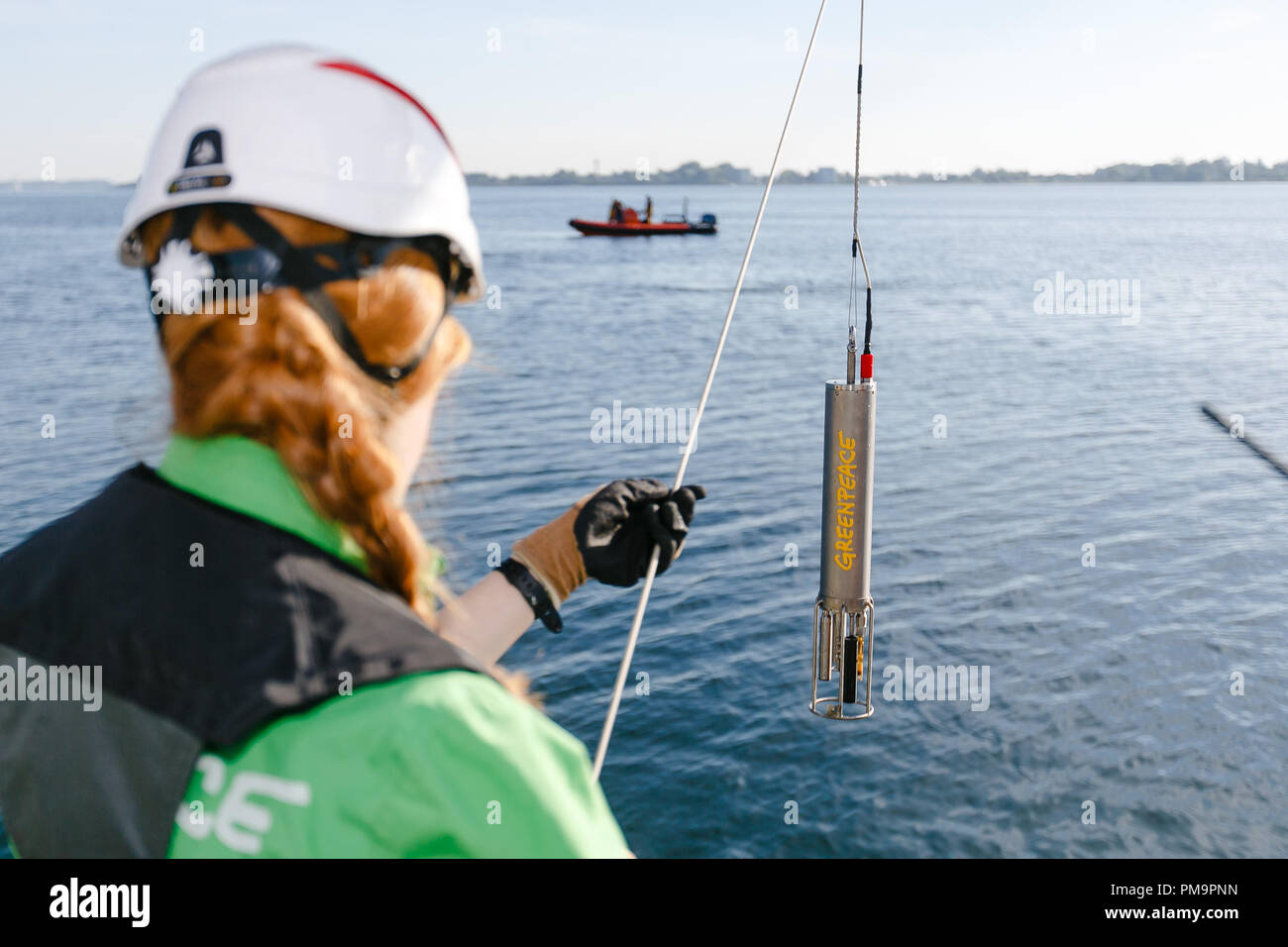 18 September 2018, Schleswig-Holstein, Gluecksburg: Student Daniela Herrmann puts a CTD probe into the water to check the salinity and temperature. At the start of the Greenpeace Marine Conservation Tour, scientists in the Flensburg Fjord took water samples and examined them for fertiliser contamination. Photo: Frank Molter/dpa - Stock Image