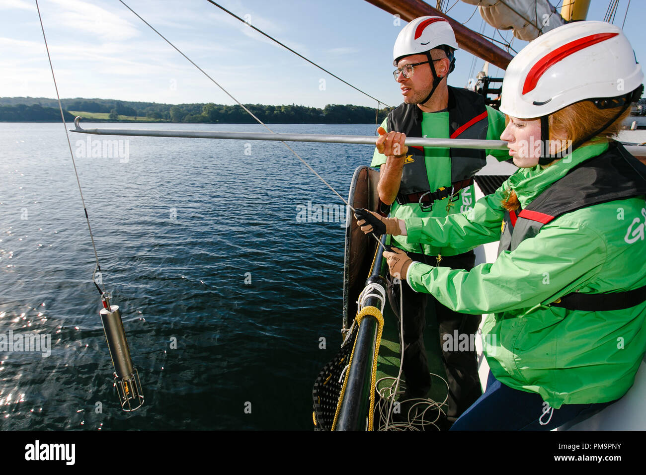 18 September 2018, Schleswig-Holstein, Gluecksburg: Agricultural biologist Dirk Zimmermann (l) and student Daniela Herrmann let a CTD probe into the water to check the salinity and temperature. At the start of the Greenpeace Marine Conservation Tour, scientists in the Flensburg Fjord took water samples and examined them for fertiliser contamination. Photo: Frank Molter/dpa - Stock Image