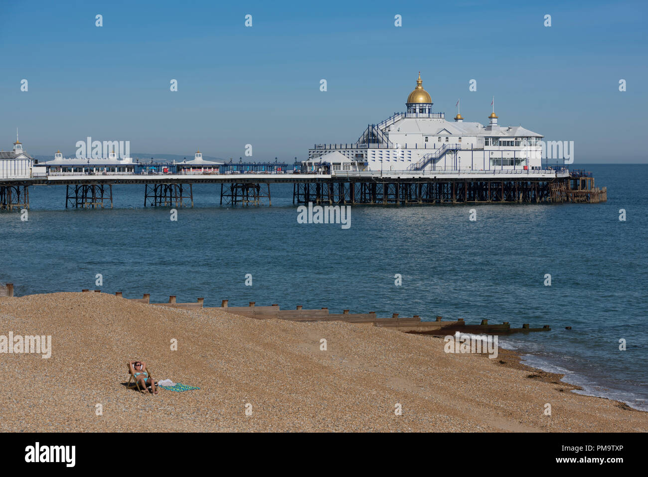 A solitary sunbather on the beach at Eastbourne in the county of East Sussex on the south coast of England with the pier behind. - Stock Image