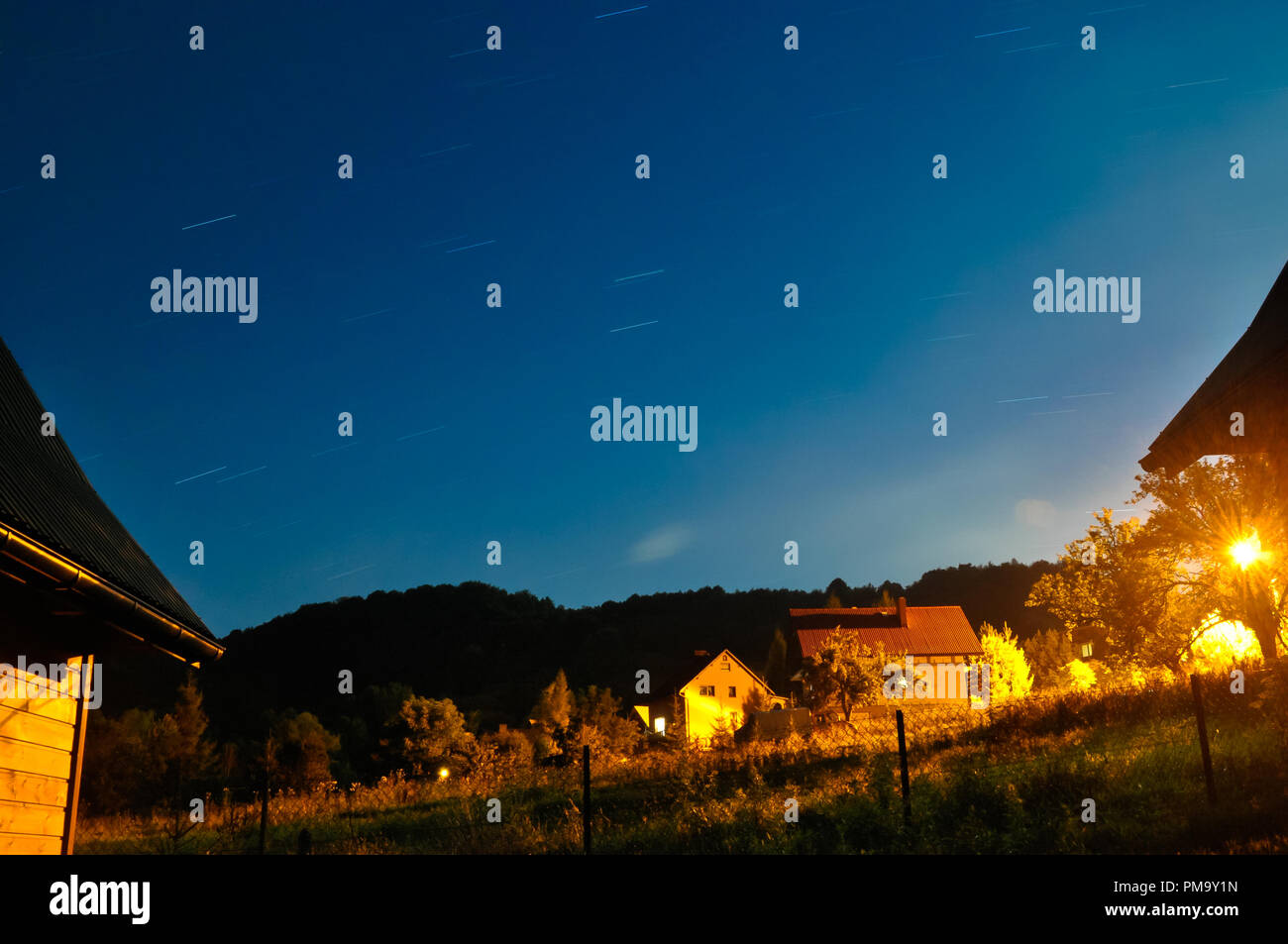 Landscape of small village and sky with stars at night with long exposure - Stock Image