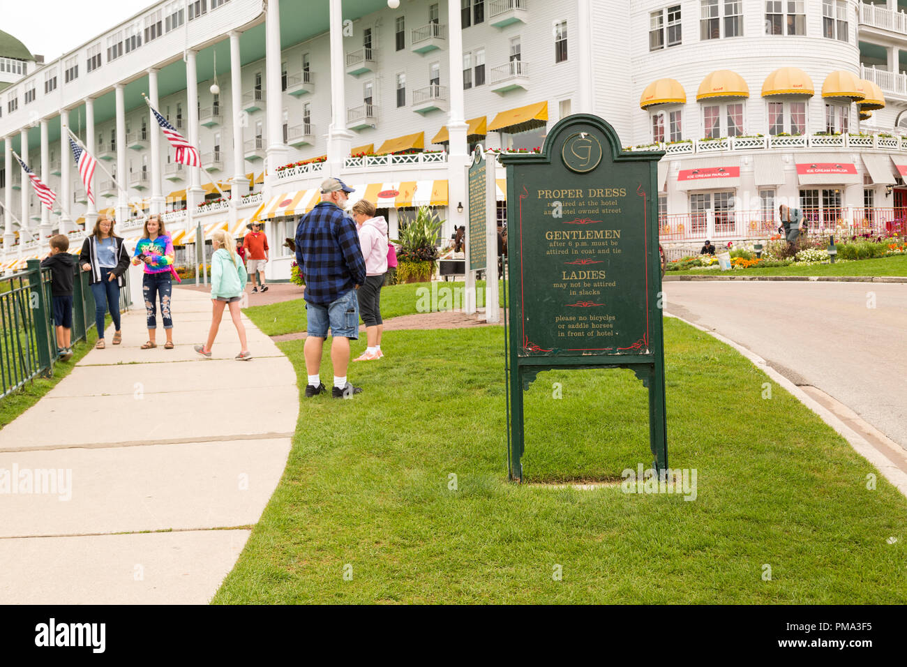 Outdoor sign with proper dress code rules, in front of the Grand Hotel resort on Mackinac Island, Michigan. The tourists  around are dressed casually. - Stock Image