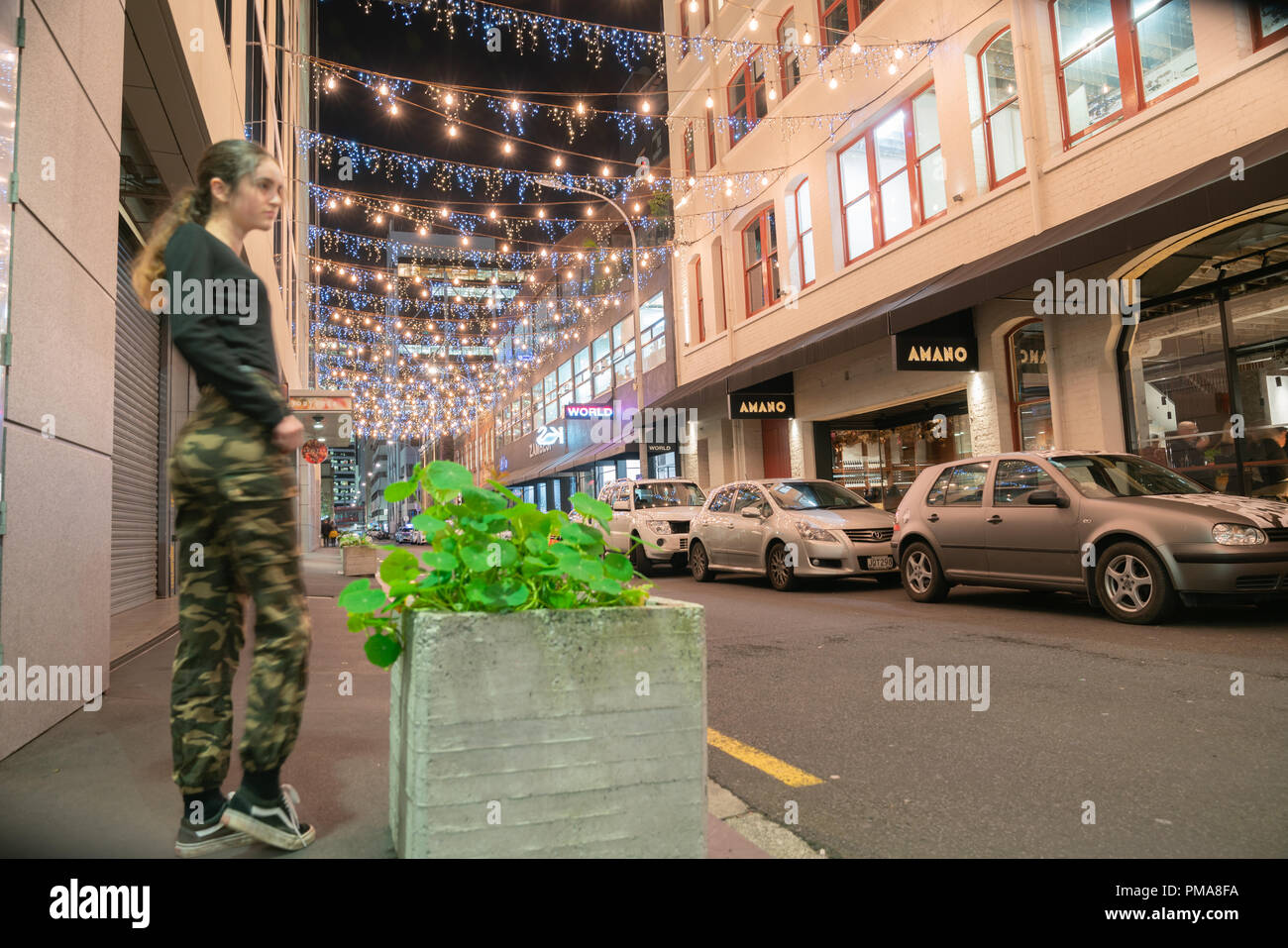 AUCKLAND, NEW ZEALAND - SEPTEMBER 14 2018; Auckland's Britomart area, bright and decorative lights, street furniture with young trendy woman  at night - Stock Image