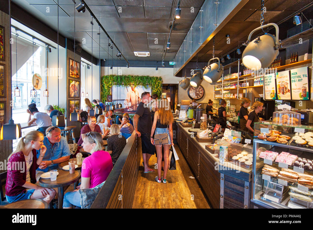 Copenhagen, Denmark-August 1, 2018: People eating in busy cafe located on Kongens Nytorv central city square - Stock Image