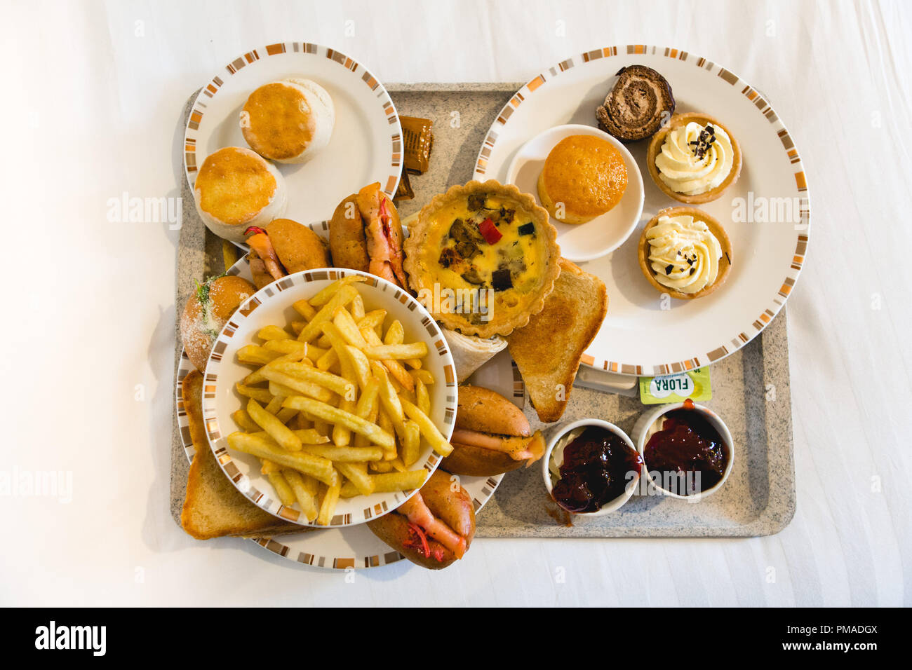 Tray full of sweet and savoury food including plates of sandwiches, rolls, cakes, pastries, scones & French fries (chips) for afternoon tea, on a bed Stock Photo