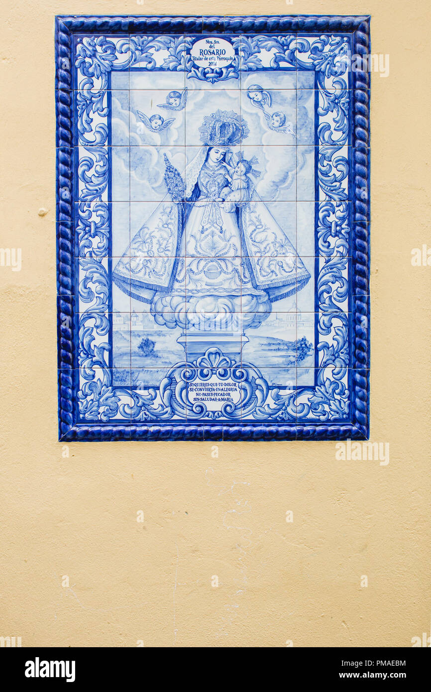 Blue glazed tiles (azulejos tiles) depicting a saintly mother and her baby looked down on by angels, set in a lemon yellow wall in an Obidos street - Stock Image