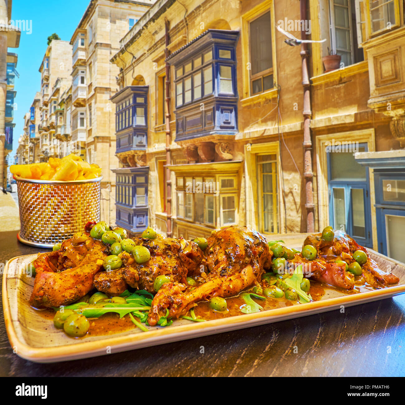 Enjoy the rabbit, stewed in red wine with beans, herbs and spices  in the popular restaurant of Strait street, Valletta, Malta. - Stock Image