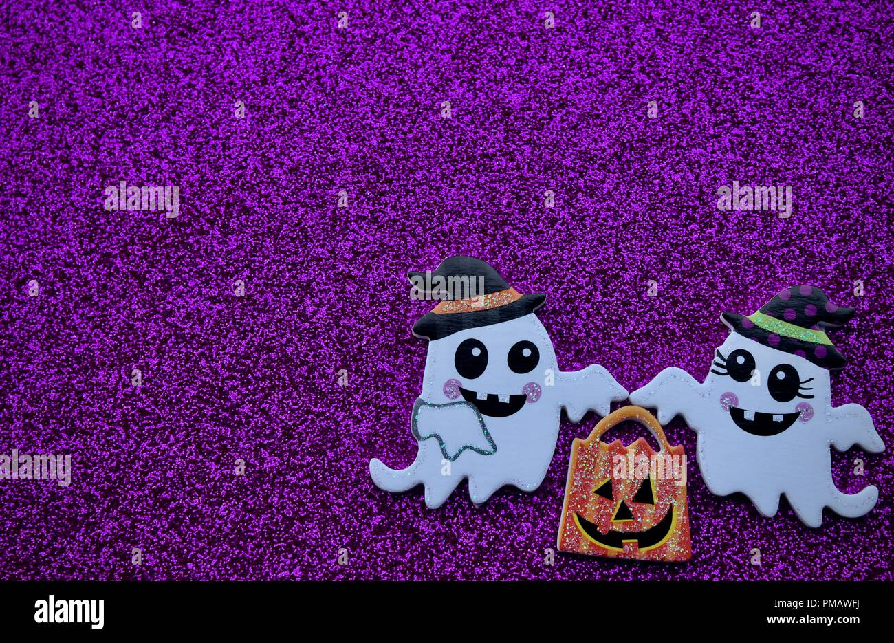 two ghosts carrying a pumpkin trick or treat bag on a purple background - Stock Image