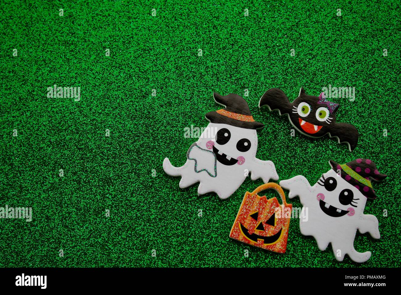 two ghosts carrying a pumpkin trick or treat bag with a black bat flying above on a green background - Stock Image