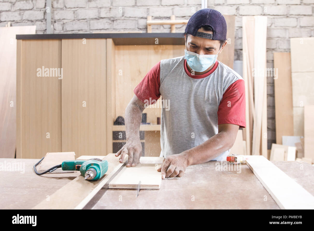 worker at carpenter workspace cutting the wood board using saw t Stock Photo