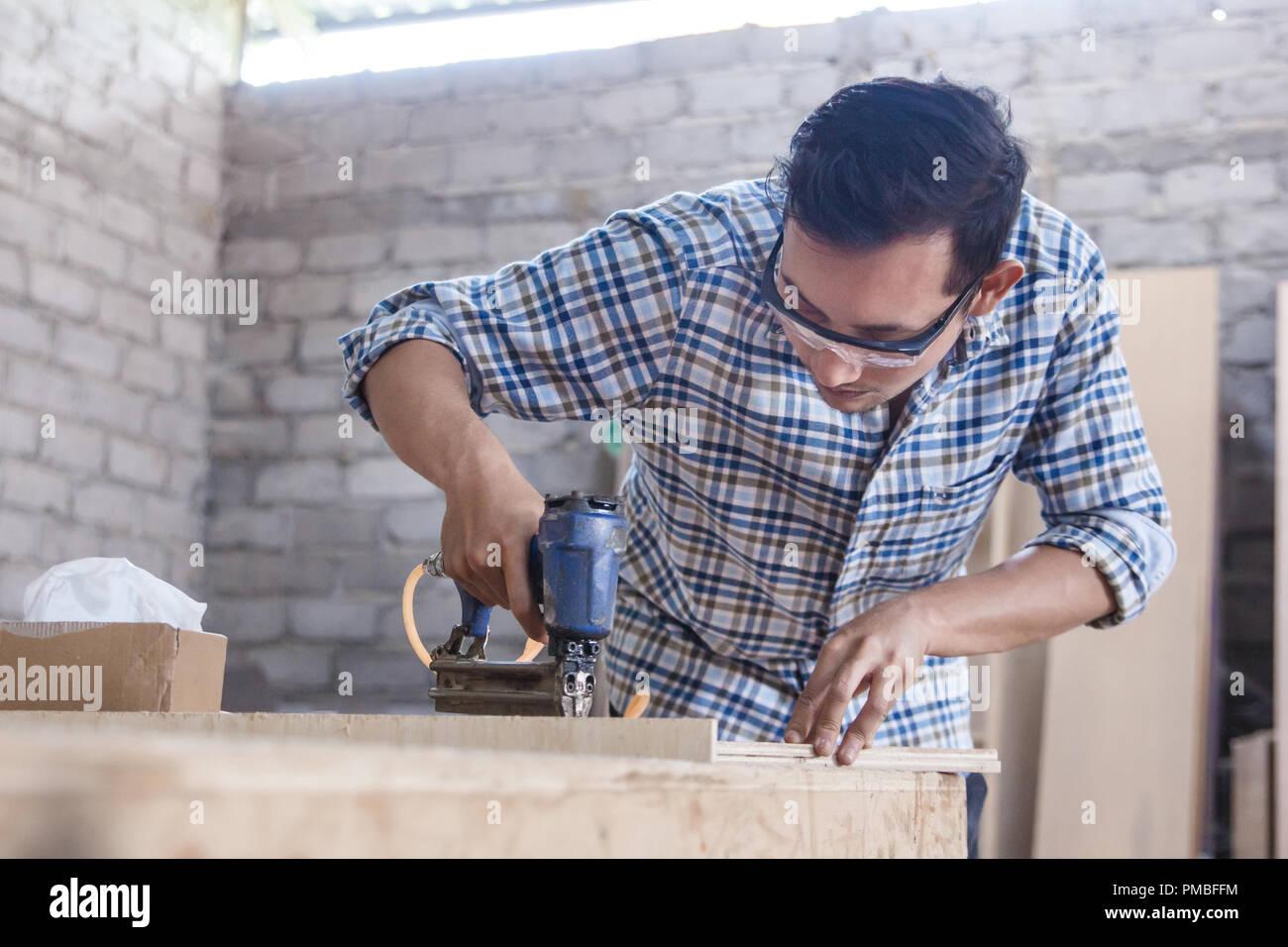 worker at carpenter workspace installing nail using pneumatic na Stock Photo