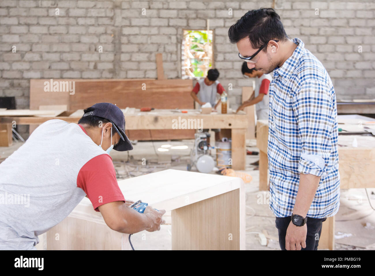 furniture factory owner controlling his worker at work space - Stock Image