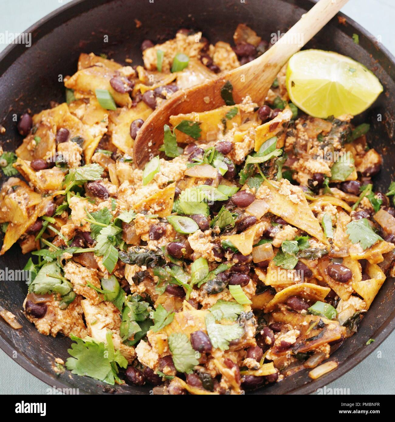 Vegan tofu scramble chilaquiles with beans, scallions and lime - Stock Image