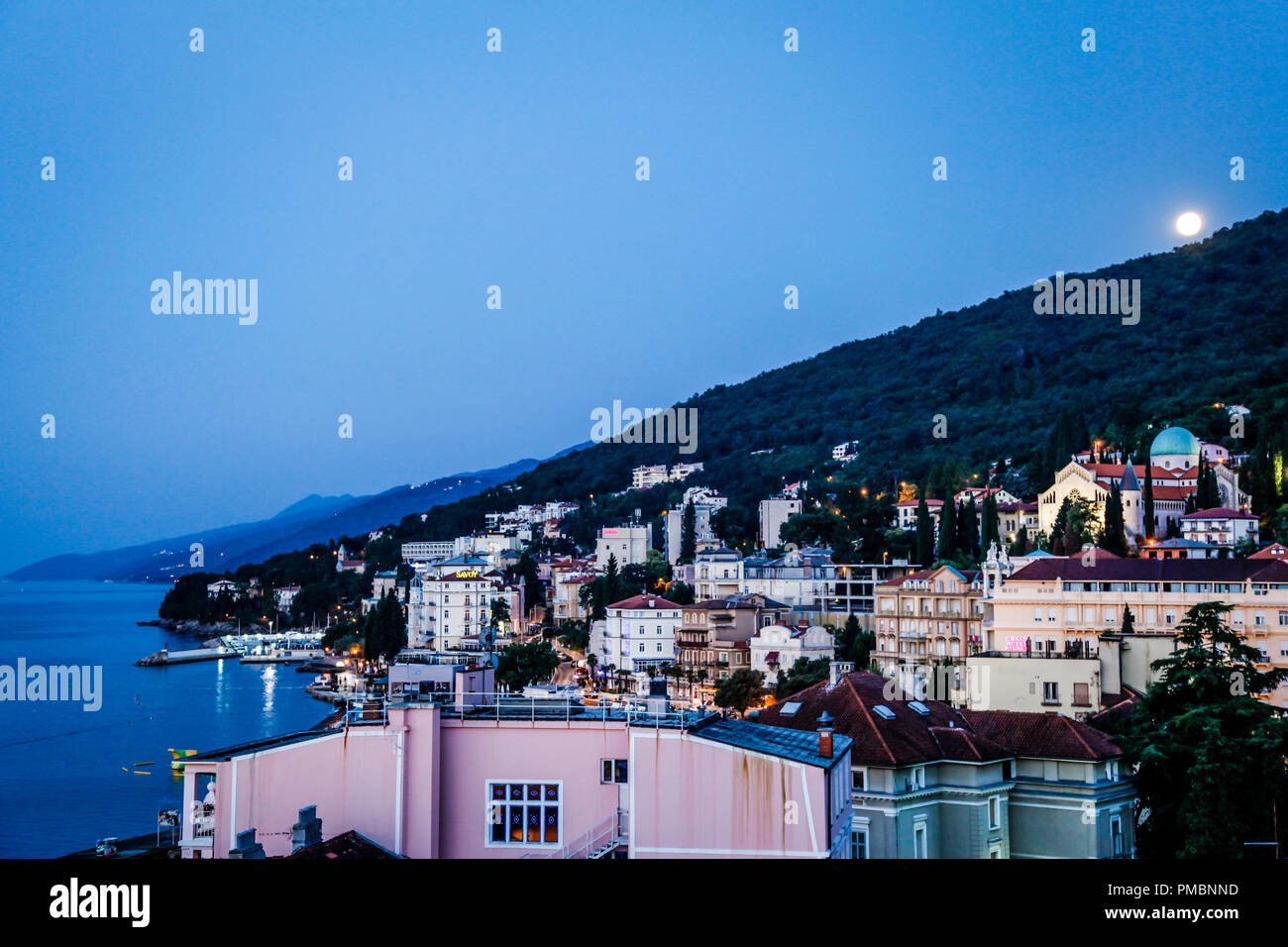 Rooftop view over the Croatian resort of Opaija Croatia as the moon rises at eventide - Stock Image