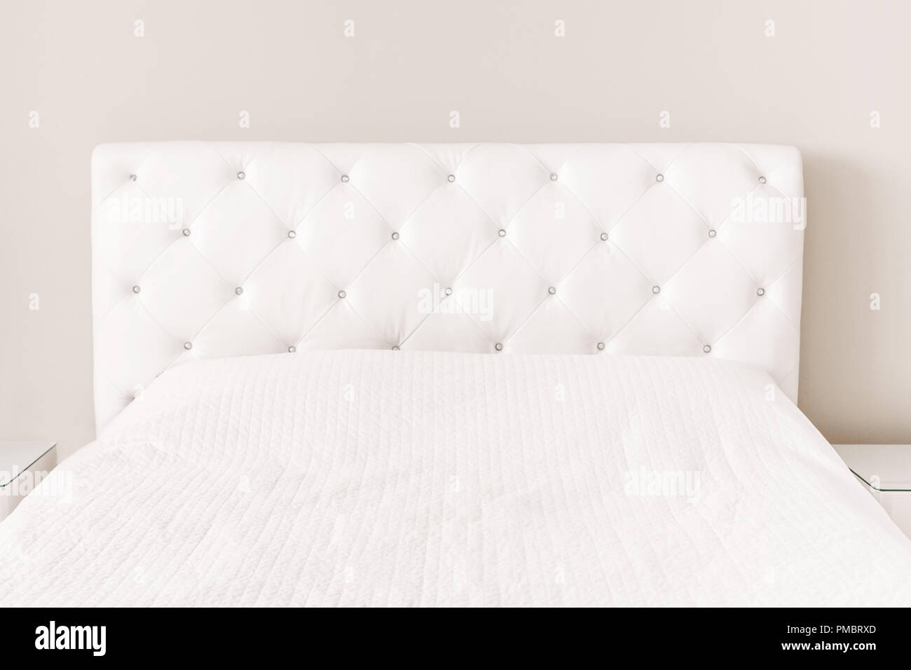 Empty White Bed With Duvet Cover Bedspread. Master Bedroom With Light  Walls. Modern Furniture At Home With Nobody. Background Mockup With  Copyspace Fo