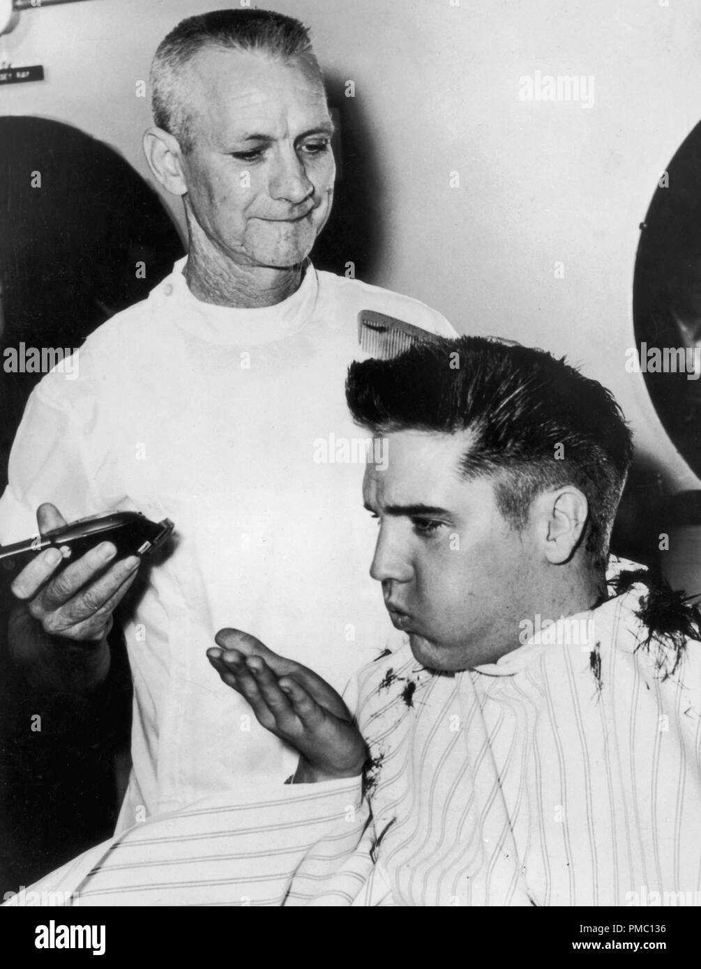 Army recruit, Elvis Presley, blows hair clippings from his hand as he sits for a haircut from an Army barber, in Fort Chaffee, Arkansas, circa 1958  File Reference # 33595_100THA - Stock Image