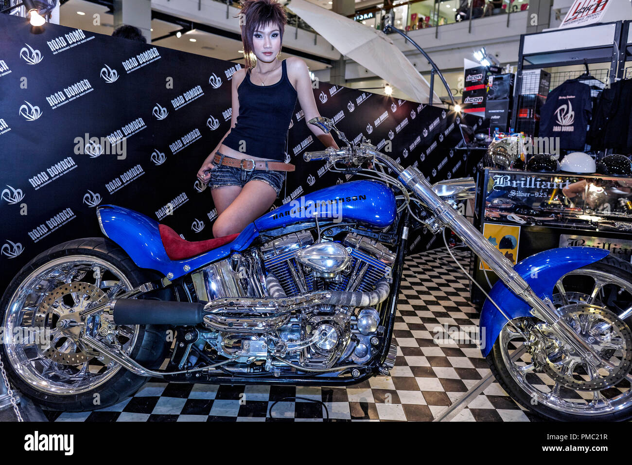 Harley Davidson customized chopper motorcycle and female model at the annual Bangkok motorcycle show. Thailand S. E. Asia - Stock Image